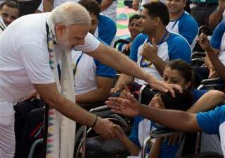 Indian Prime Minister Narendra Modi reaches out for a child who was amongst the thousands who performed yoga on occasion of World Yoga Day in Chandigarh