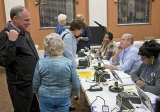 Democratic vice presidential candidate US Senator Tim Kaine receives his ballot from a poll worker as he and his wife, Anne Holton vote in Richmond