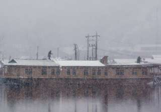 Kashmiri boatmen clear snow from the roof of their houseboat as it snows in Srinagar.