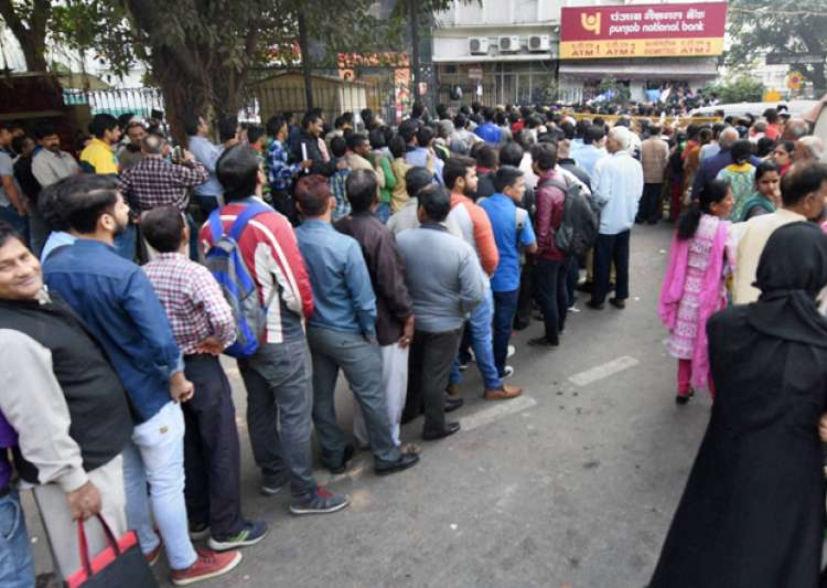 People stand in queue out a bank in New Delhi - India Tv