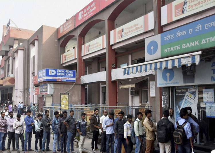 People stand in a long queue to withdraw money at an ATM in- India Tv