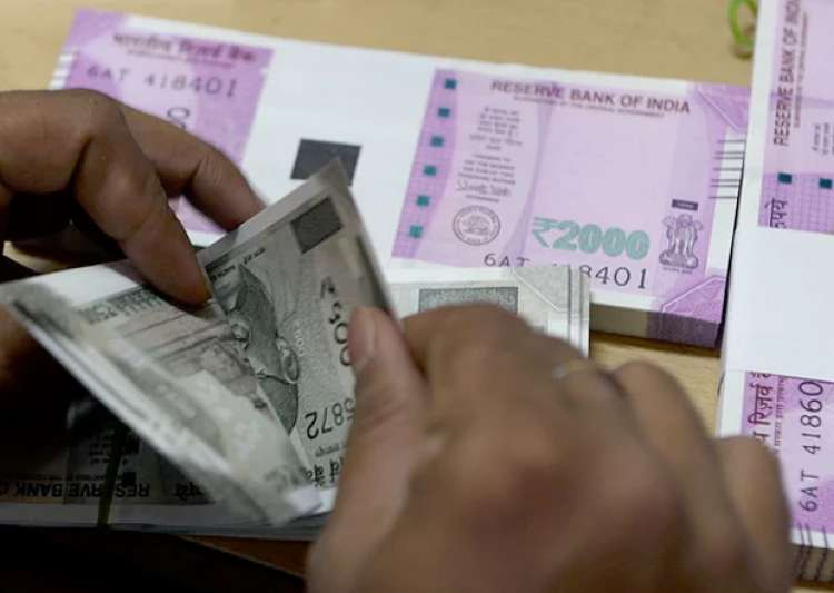 A bank employee counts new notes of Rs 500 and Rs 2000- India Tv