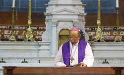 Archbishop of Delhi, Anil Couto, reads from a holy book