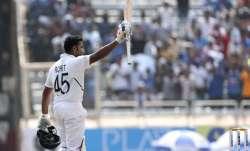 India's Rohit Sharma raises his bat to acknowledge the