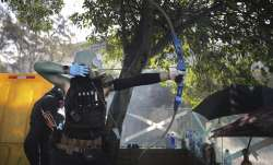 A protestor prepares to fire a bow and arrow during a confrontation with police at the Hong Kong Pol