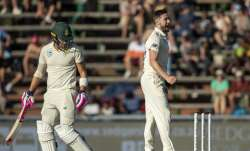 England's bowler Chris Woakes, right, celebrates after