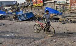 A boy walks past a neighbourhood vandalised by rioters