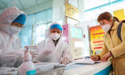 Medical workers in protective gear talk with a woman who