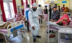 Sanitation worker sprays disinfectants inside a hospital in