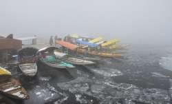 Boatmen stand near their Shikaras during a cold and foggy morning, in Srinagar