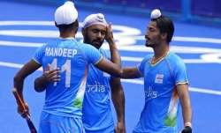 India's Mandeep Singh celebrates after India's Simranjeet Singh scores against Spain.