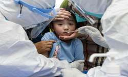 FILE   A child reacts to a throat swab during mass testing